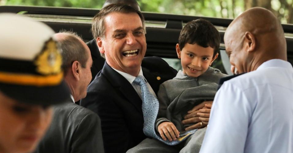O presidente eleito, Jair Bolsonaro, carrega o menino Miguel dos Santos, 9, que esperava Bolsonaro deixar o comando da Aeronáutica após se encontrar com comandantes militares, em Brasília.