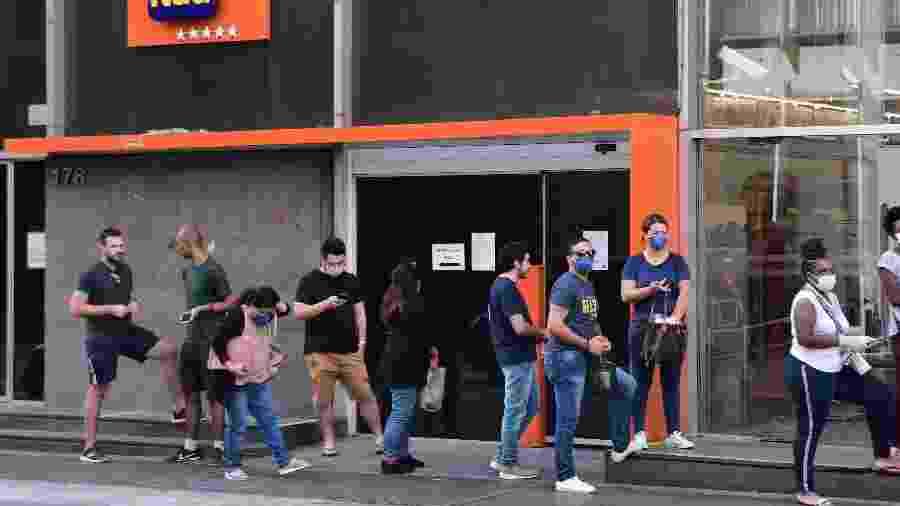 30.mar.2020 - Fila de pessoas usando máscaras de proteção ao coronavírus no centro de São Paulo - Ettore Chiereguini/Futura Press/Estadão Conteúdo