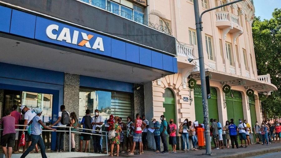 Fila de pessoas em frente à Caixa Econômica Federal esperando para receber o auxílio emergencial - Getty Images
