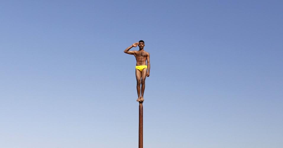 """Soldado do Exército indiano executa a """"malkhamb"""", a ginástica tradicional do país, durante um programa de sensibilização para atrair jovens para ingressar nas Forças Armadas, na véspera do Dia da República da Índia em Gandhinagar, no Estado de Gujarat"""