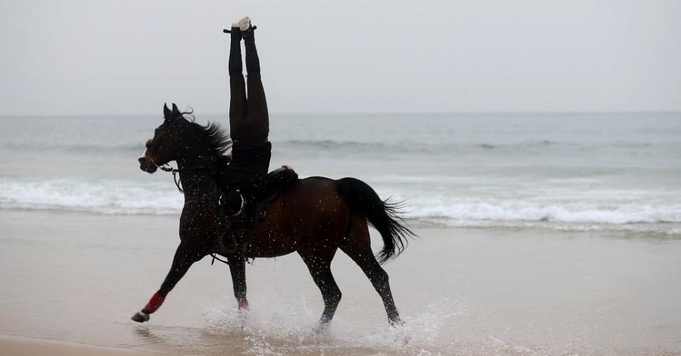 25.mar.2016 - Abdullah al-Ghifari, um cavaleiro palestino de 23 anos anda a cavalo de ponta-cabeça na praia da cidade de Gaza