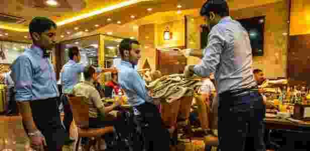 - Garçom carrega kebabs servidos no restaurante Haji Hussein, em Bagdá, no Iraque - Bryan Denton/The New York Times - Bryan Denton/The New York Times