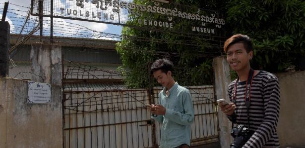 Jovens jogam Pokémon Go na entrada do museu do genocídio Tuol Sleng