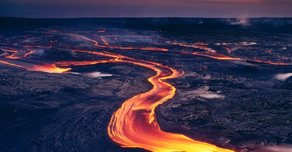 Um rio de lava escorre do vulcão Pu'u 'O'o, no Havaí. Este vulcão, em erupção contínua desde 1983, já aumentou a ilha em mais de 2 km², mas também destruiu centenas de casas