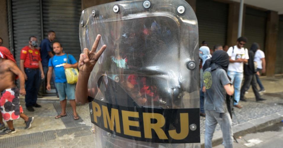 9.fev.2017 - Jovem segura escudo da polícia militar do Rio em meio a confronto entre policiais e manifestantes no Centro da cidade, perto da Alerj