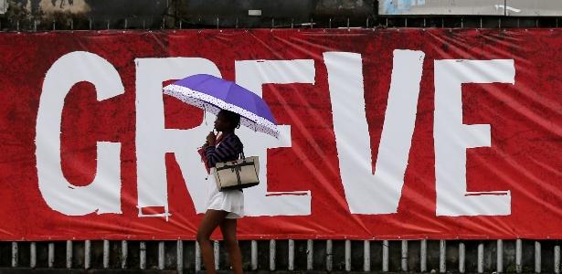 """Mulher passa em frente a uma faixa com os dizeres """"greve geral"""", no Rio - Sergio Moraes/Reuters"""