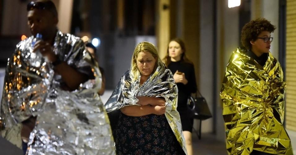 3.jun.207 - Pessoas se protegem com mantas térmicas distribuídas por socorristas em área próxima à London Bridge, local onde ocorream ataques considerados como atos de terrorismo pela polícia londrina