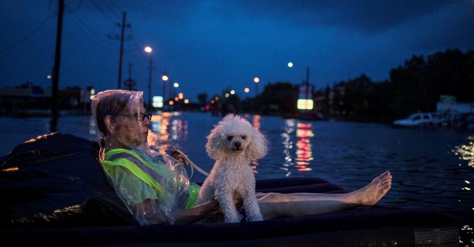 27.ago.2017 - Mulher aguarda resgate em colchão de ar com seu cachorro durante a enchente provocada pela tempestade Harvey em Houston