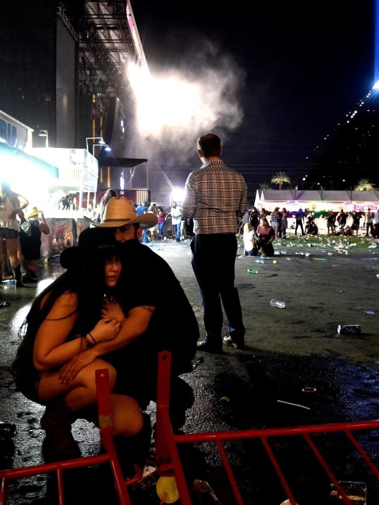 1º.out.2017 - Casal se agacha para se proteger durante ataque em festival em Las Vegas
