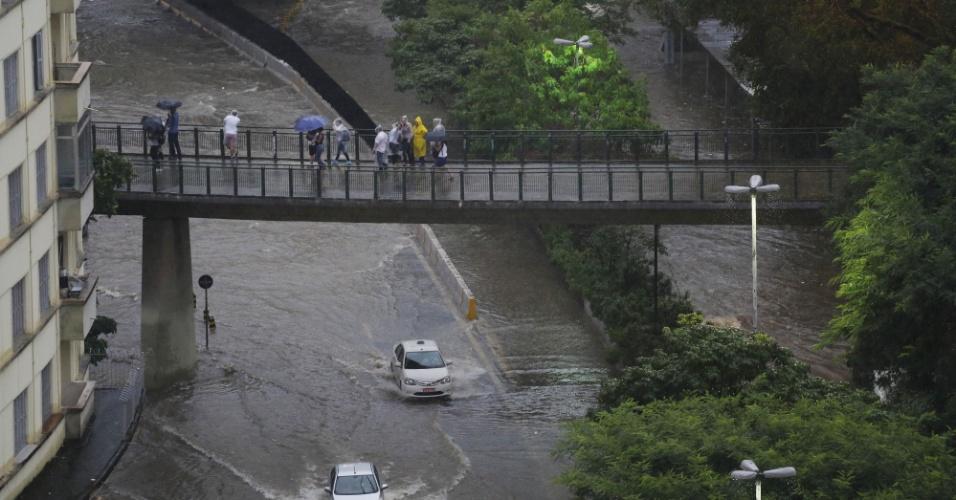 20.mar.2018 - Pedestres observam pontos de alagamento na avenida Nove de Julho, próximo à praça da Bandeira, durante forte chuva que atinge a região central de São Paulo na tarde desta terça-feira