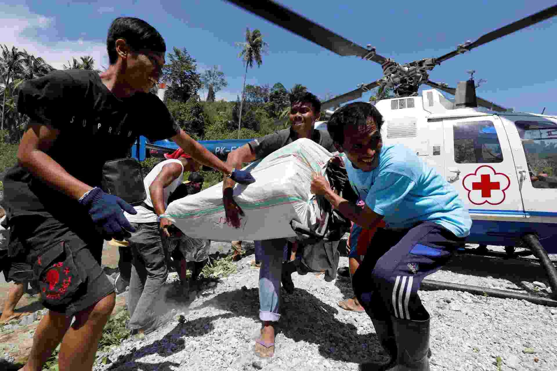 5.out.2018 - Aldeões afetados pelo terremoto do dia 28 carregam ajuda de um helicóptero da Cruz Vermelha em Biromaru, ao sul da cidade de Palu - Darren Whiteside/Reuters