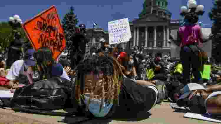 Multidão participa de de uma manifestação ao lado do Capitólio de Denver, no Estado do Colorado com as mãos atadas nas costas - Getty Images - Getty Images