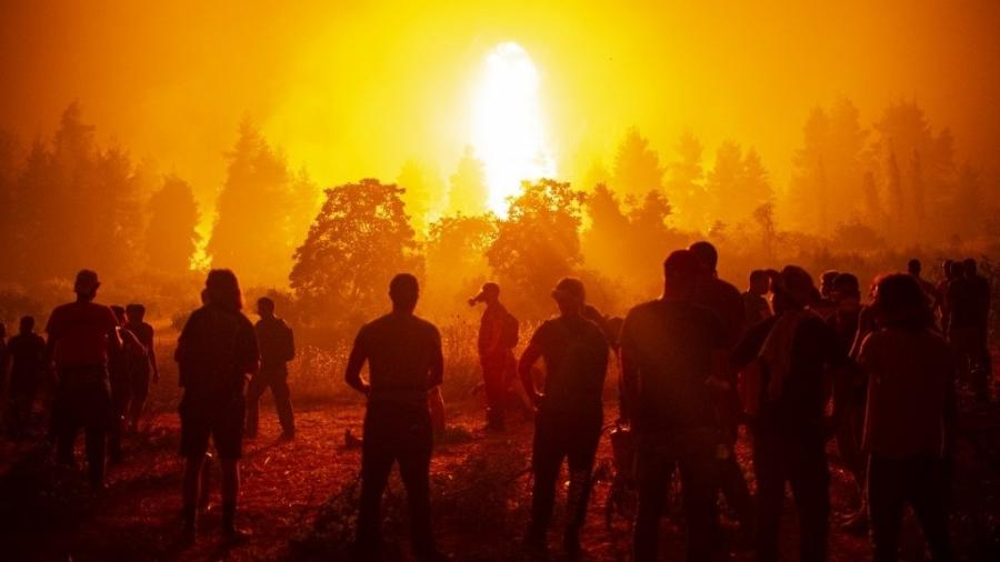 Bombeiros e voluntários lutam para conter incêndio próxima à vila de Kamatriades, no norte da ilha de Eubeia, na Grécia - Angelos Tzortzinis/AFP