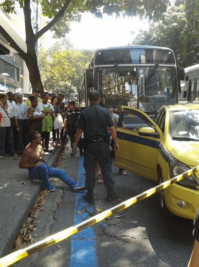 25.set.2015 - Segundo o relato da publicitária Luciana Passos, autora da foto, o taxista sentado na calçada foi esfaqueado pelo motorista do ônibus que teria sido
