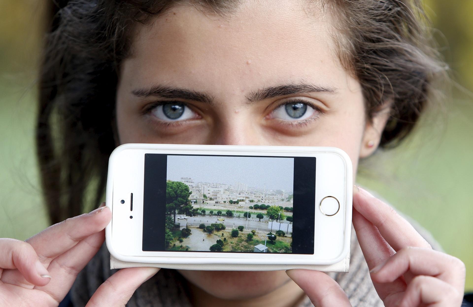 Haya, de Artoz, na Síria, mostra uma imagem de sua cidade enquanto aguarda para cruzar a fronteira da Eslovênia com a Áustria
