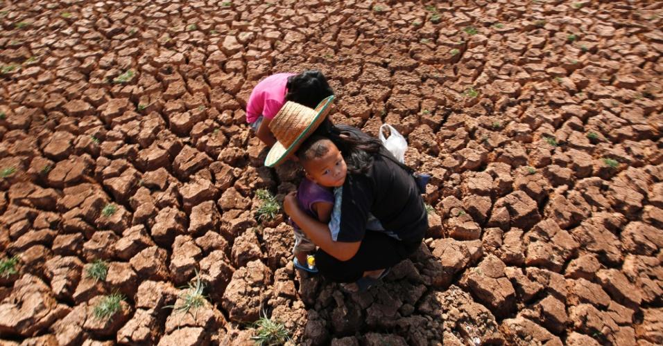 17.jan.2016 - Junto com os filhos, mulher caça caramujos e outros animais que possam servir de alimento no leito de lago seco em Udon Thani, na Tailândia. O país vem enfrentando uma mudança no padrão climático, que tem provocado longos períodos de seca