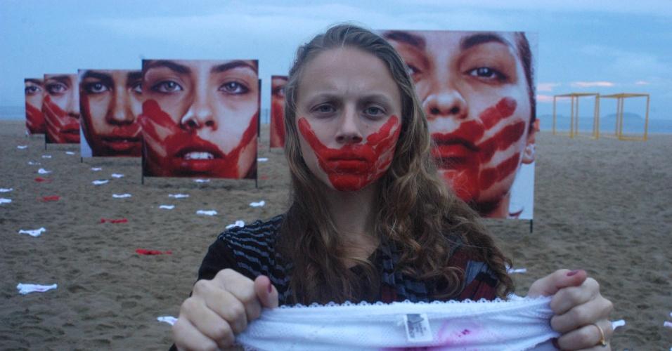 6.jun.1016 - Ativistas da ONG Rio de Paz fazem ato público para lembrar o abuso sofrido contra as mulheres, na praia de Copacabana, no Rio de Janeiro. Vinte painéis foram fixados na areia com rostos femininos marcados de vermelho. Além disso, 410 calcinhas, nas cores vermelho e branco, foram espalhadas no local
