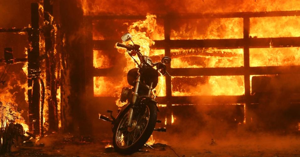 9.out.2017 - Motocicleta queima na frente de uma das residências atingidas pelas chamas em Glen Ellen, Califórnia