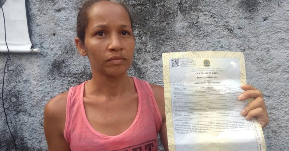 12.fev.2019 - Mãe de uma das vítimas do Fallet mostra a certidão de óbito do filho de conta viver sob ameaça