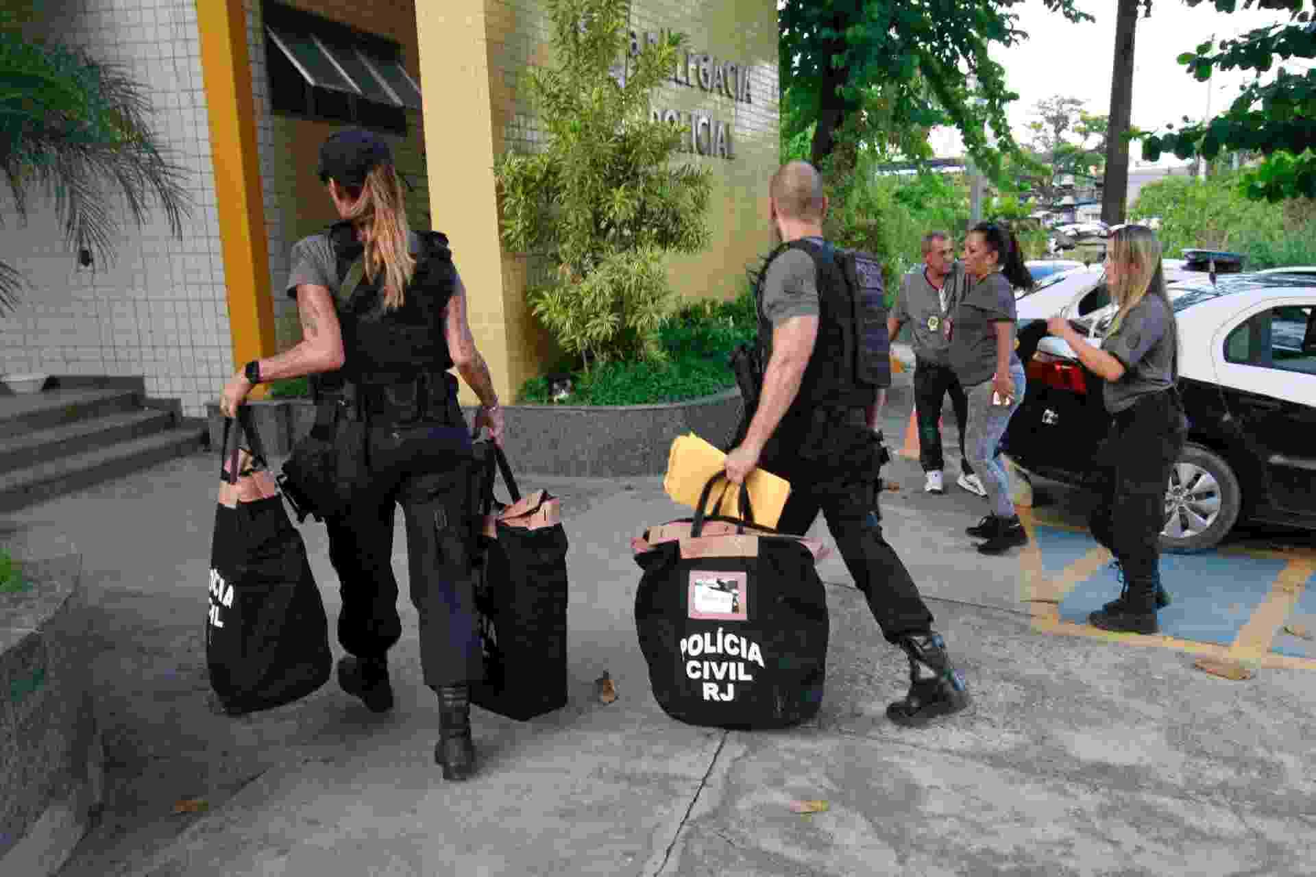 2.mai.2019 - Policiais chegam à 16º DP na Barra da Tijuca, no Rio de Janeiro (RJ), carregando malotes com documentos aprendidos na associação de moradores da Muzema - Jose Lucena/Futura Press/Estadão Conteúdo