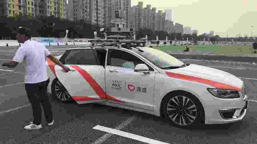 Homem abre a porta do carro autônomo da empresa chinesa Didi - Josh Horwitz/Reuters