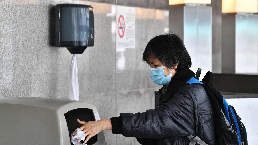 4.fev.2020 - Mulher joga fora papel usado para secar as mãos depois de lavá-las no Hospital Princess Margaret, em Hong Kong - Anthony Wallace/AFP