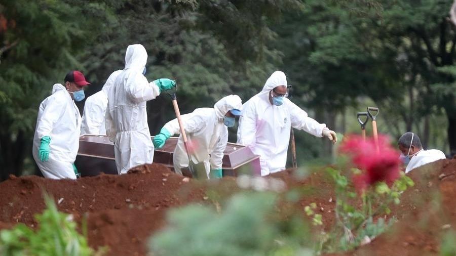 3.abr.2020 - Funcionários do serviço funerário enterram corpo de uma vítima do novo coronavírus no cemitério da Vila Formosa, em São Paulo - Fernando Bizerra/EFE