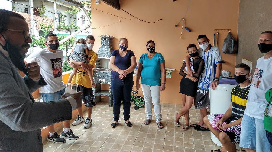 O ouvidor da Polícia, Elizeu Soares Lopes (de terno), conversa com os jovens Eryk (com uma criança no colo), Kelvin (abraçado com a esposa) e Alexssandro (sentado) e seus pais - Marcelo Oliveira/UOL