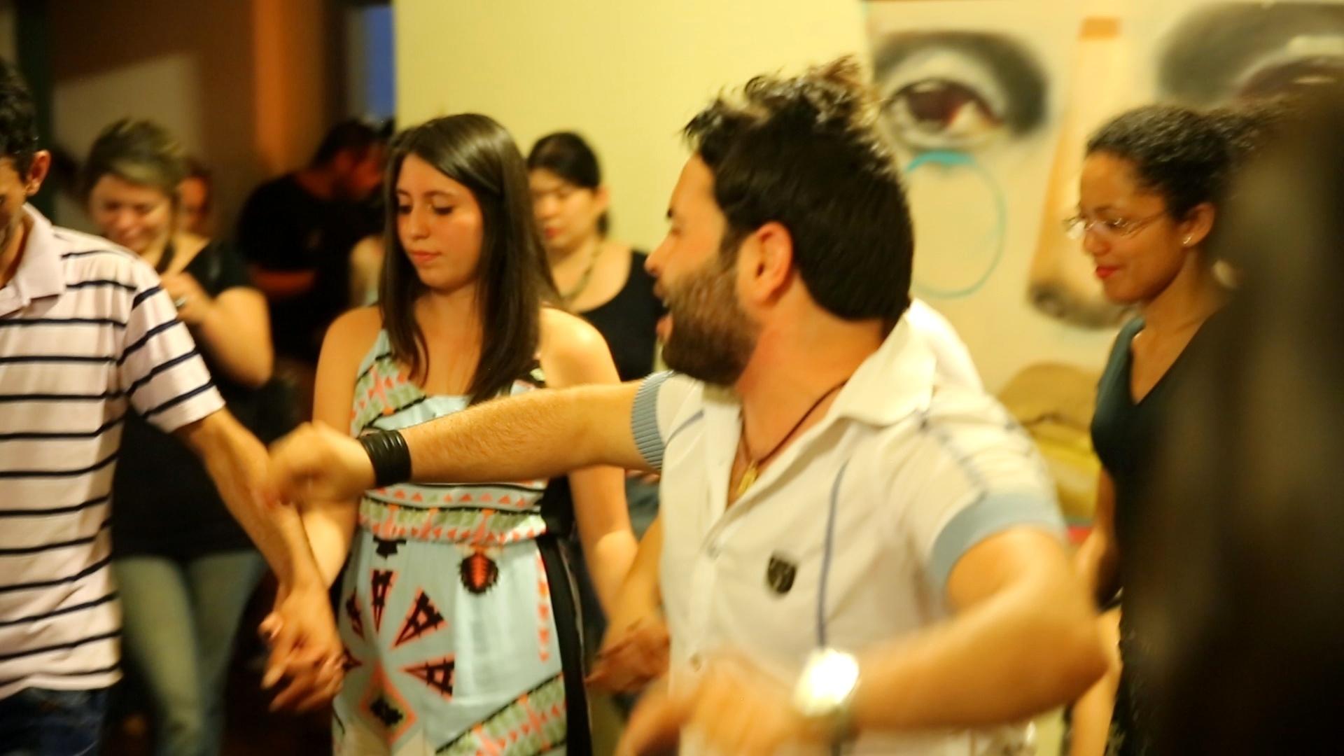 Refugiado sírio mostra alguns passos da dança tradicional síria para alunos da ONG Abraço Cultural em aula cultural em São Paulo