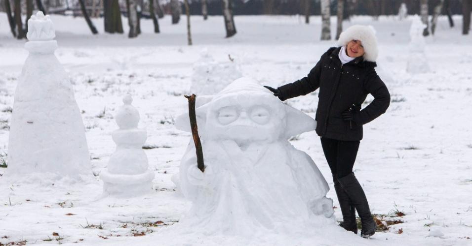 """10.jan.2016 - Garota posa ao lado de escultura de neve de Yoda, personagem da saga """"Star Wars"""", durante festival em Chisinau, na Moldova"""