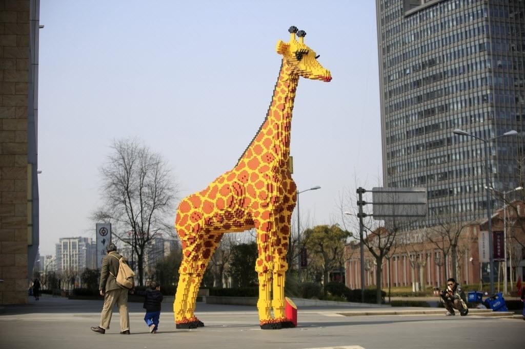 1°.mar.2016 - Uma girafa feita de Lego foi montada ao lado de um shopping em Xangai, na China. O animal de brinquedo tem 6,16 metros de altura e foi feito em 450 horas com 40 mil peças