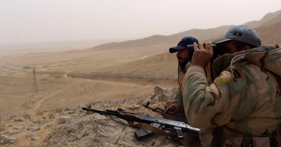 25.mar.2016 - Tropas sírias monitoram a periferia da cidade de Palmira, na Síria, retomada pelas forças leais a Bashar al-Assad após batalha com os jihadistas do Estado Islâmico, que controlavam o território. O Exército sírio contou com apoio de aviões russos e milícias rebeldes para derrotar os terroristas