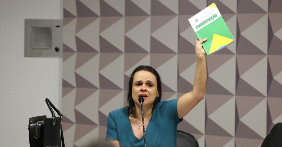 28.abr.2016 - A jurista Janaína Paschoal ergue um exemplar da Constituição durante sessão da comissão especial de impeachment no Senado