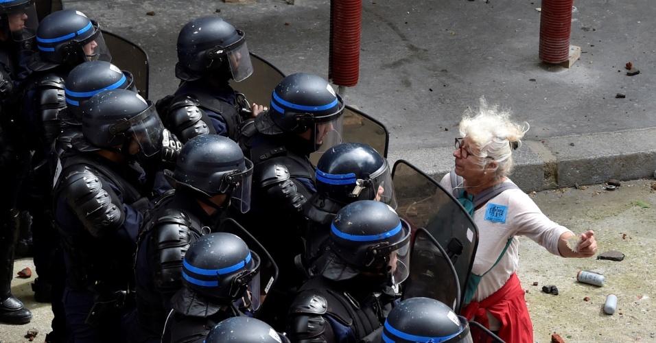 14.jun.2016 - Mulher enfrenta cordão de policiais que bloqueiam o acesso a uma rua, durante protesto contra reformas trabalhistas em Paris, na França
