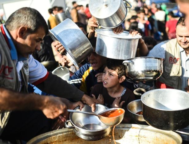 Refugiados iraquianos recebem comida no campo de Khazir, entre Irbil e Mossul