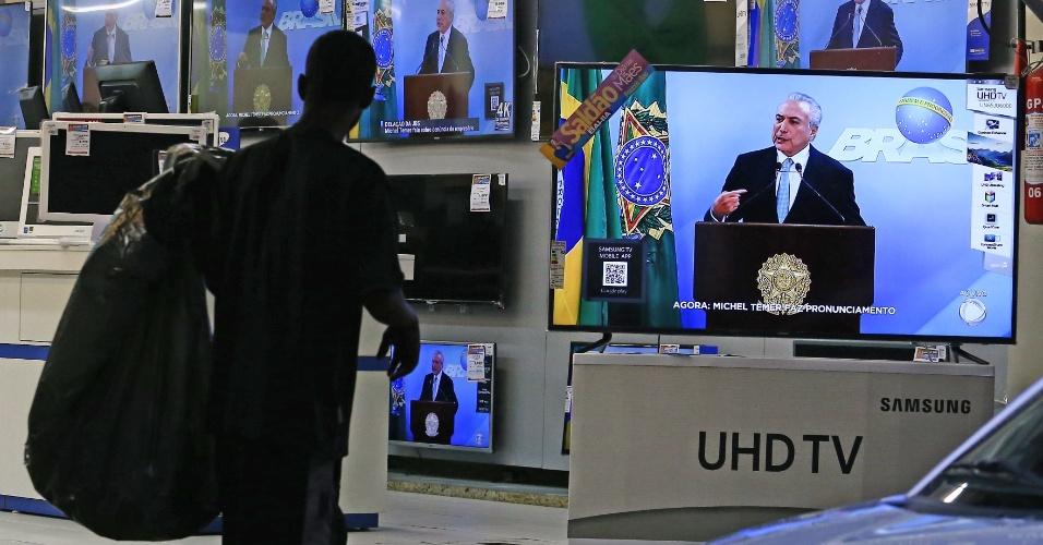 Um homem assiste ao pronunciamento do presidente Michel Temer em lojas de eletrodomésticos no centro do Rio de Janeiro