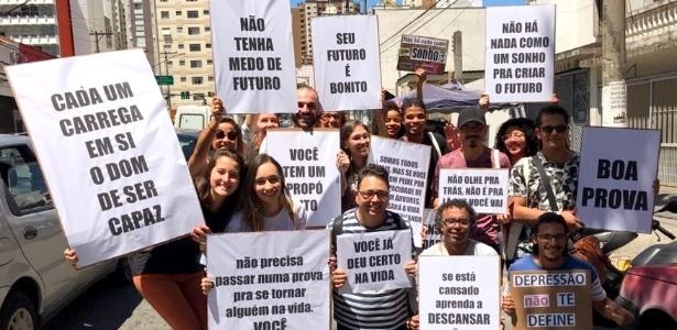 Grupo com cartazes com mensagens motivadoras e que promete cordão para ajudar atrasados