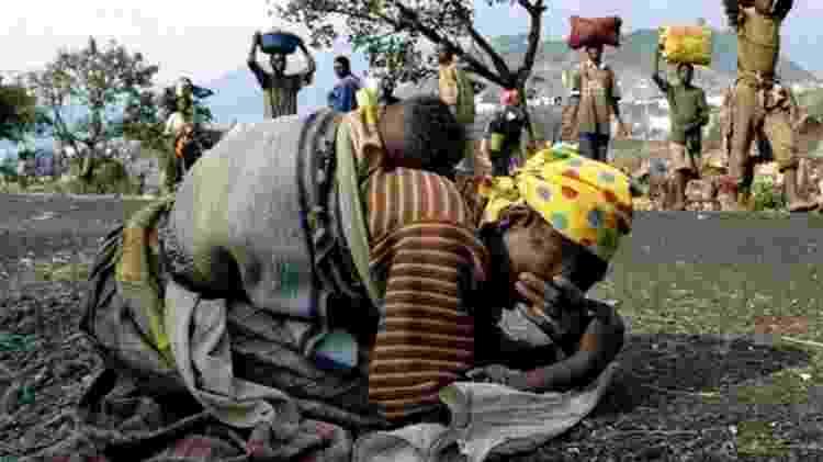 Mulher desaba aos prantos, com o bebê nas costas, após fugir de Ruanda em 1994 -  Reuters