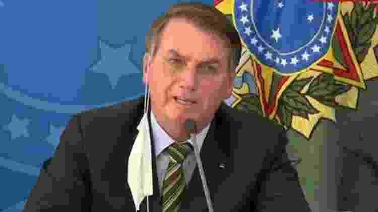 Jair Bolsonaro (sem partido) usa a máscara pendurada na orelha durante coletiva sobre coronavírus - Reprodução/GloboNews - Reprodução/GloboNews