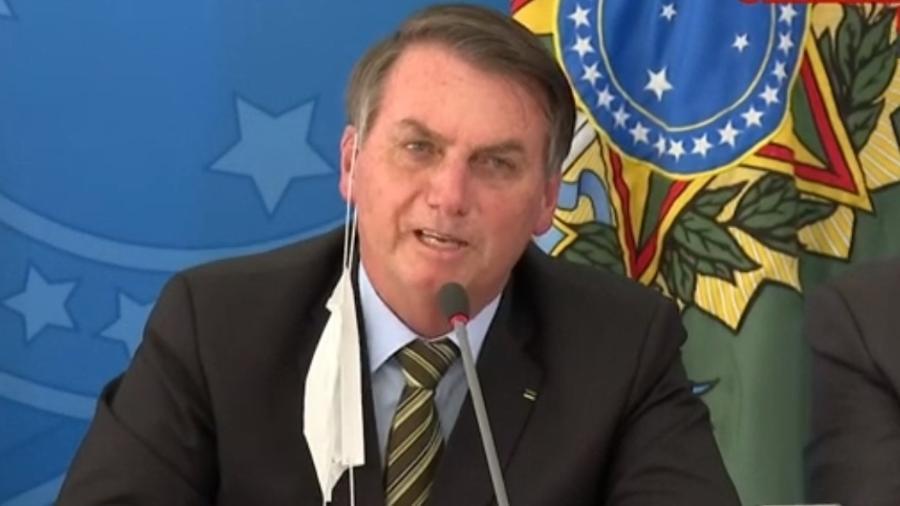 Jair Bolsonaro (sem partido) usa a máscara pendurada na orelha durante coletiva sobre coronavírus - Reprodução/GloboNews