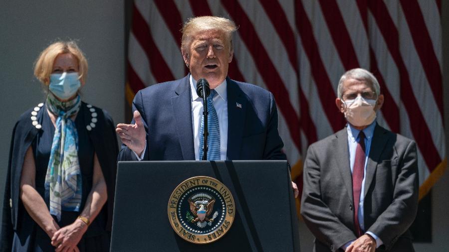 Donald Trump, sem máscara, discursa sobre o coronavírus em frente aos médicos Deborah Birx e Anthony Fauci, que usam máscaras - Drew Angerer/Getty Images