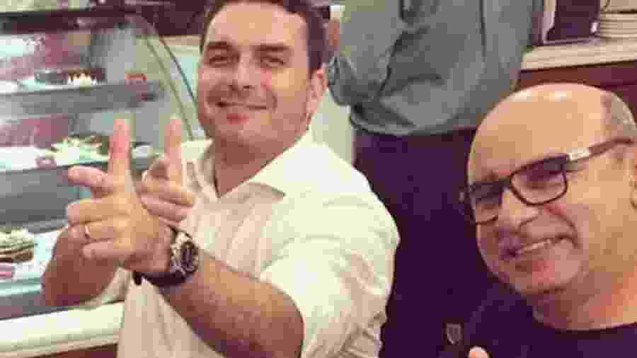 """Flávio Bolsonaro e Fabrício Queiroz fazem """"arma"""" com as mãos - Reprodução"""