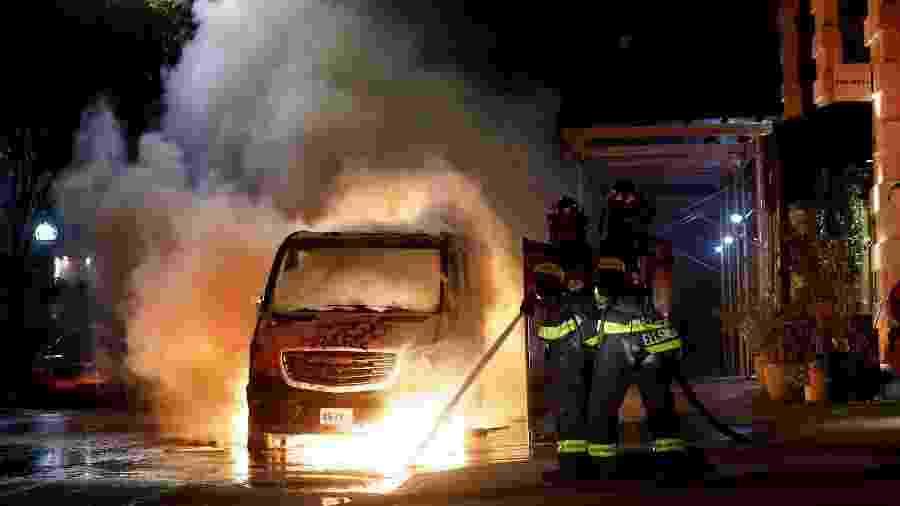 30.mai.2020 - Bombeiros apagam fogo em carro incendiado durante protestos pela morte de George Floyd em Nova York - Justin Lane/Efe
