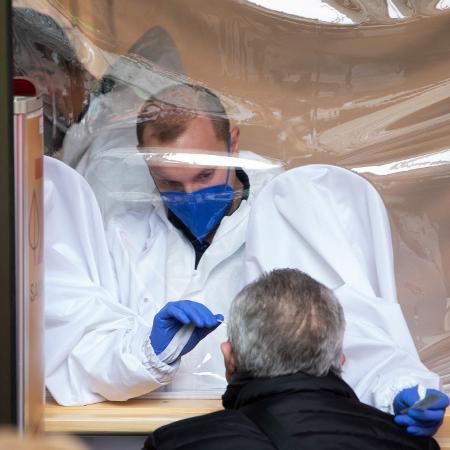 8.fev.2021 - Profissional de saúde faz teste em homem em farmácia em Viena, na Áustria - Alex Halada/AFP