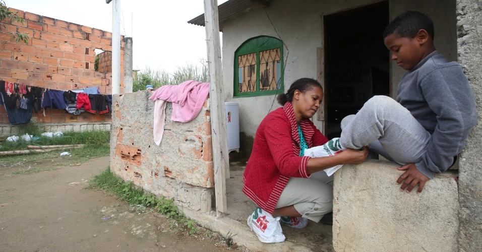 6.jul.2015 - A empregada doméstica Antenora Deonice, 43, que mora ao lado do terreno onde foi construído o Campus Fidei (Campo da Fé) da JMJ (Jornada Mundial da Juventude) de 2013, em Guaratiba, na zona oeste do Rio de Janeiro, coloca saco plástico de mercado nos pés de um dos filhos