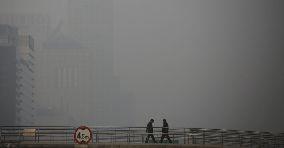 3.jan.2016 - Pedestres atravessam passarela no centro de Beijing, capital da China. A cidade voltou a ficar coberta por uma pesada névoa causada pela poluição