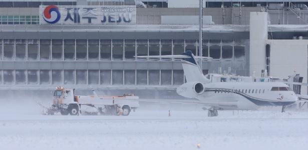 24.jan.2016 - Neve é retirada de pista do aeroporto de Jeju, na Coreia do Sul