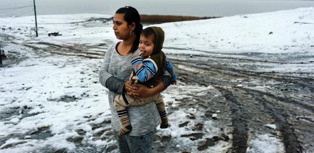 Mulher cigana carrega bebê em vilarejo coberto de neve perto de Burgas, na Bulgária