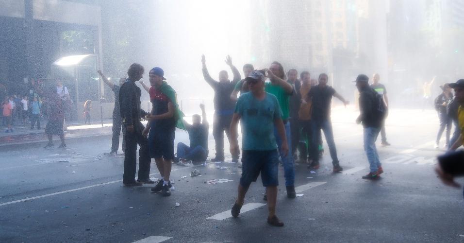 18.mar.2016 - Manifestantes que acampavam na avenida Paulista resistem ao jato de água jogado pela Tropa de Choque da Polícia Militar para liberar a via. Um ato pró-governo está marcado para às 16h e a polícia tenta evitar conflitos na região central de São Paulo