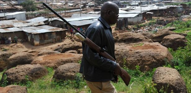 Membro do Serviço de Vida Selvagem do Quênia carrega arma com tranquilizadores em busca por leões que escaparam do parque nacional de Nairóbi em direção à cidade